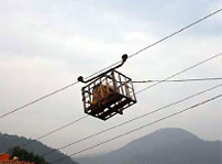 Photo: Hira watching a load transported on the ropeway.